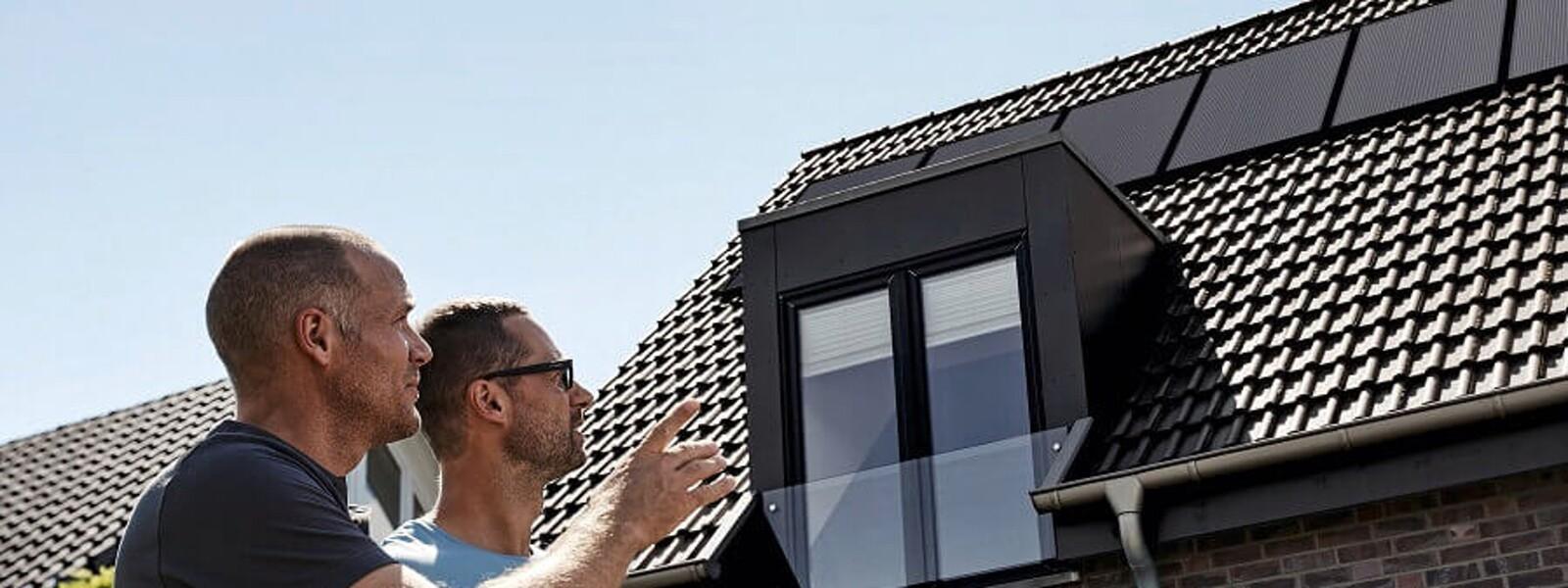Zwei Männer schauen auf ein Dach, auf dem eine Photovoltaikanlage platziert ist