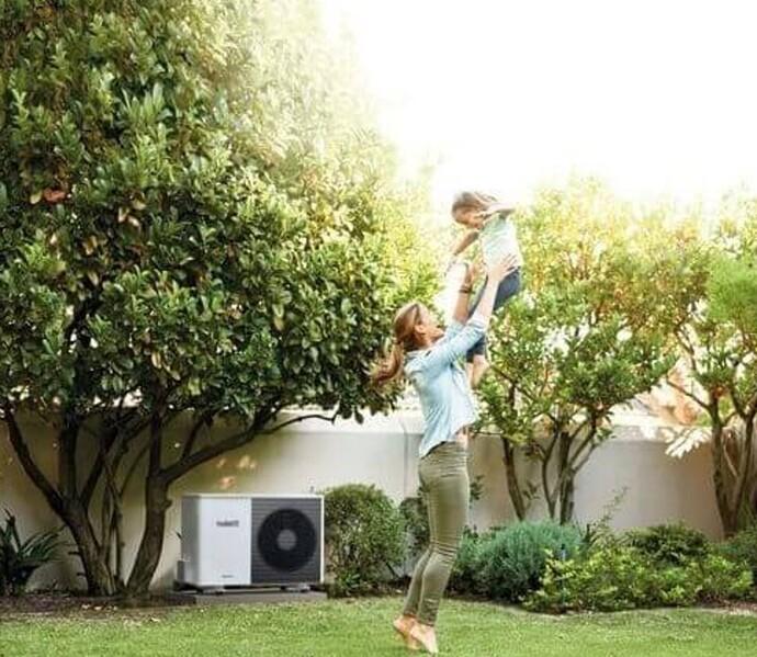 Mutter spielt mit Tochter im Garten, dahinter steht eine Vaillant Wärmepumpe
