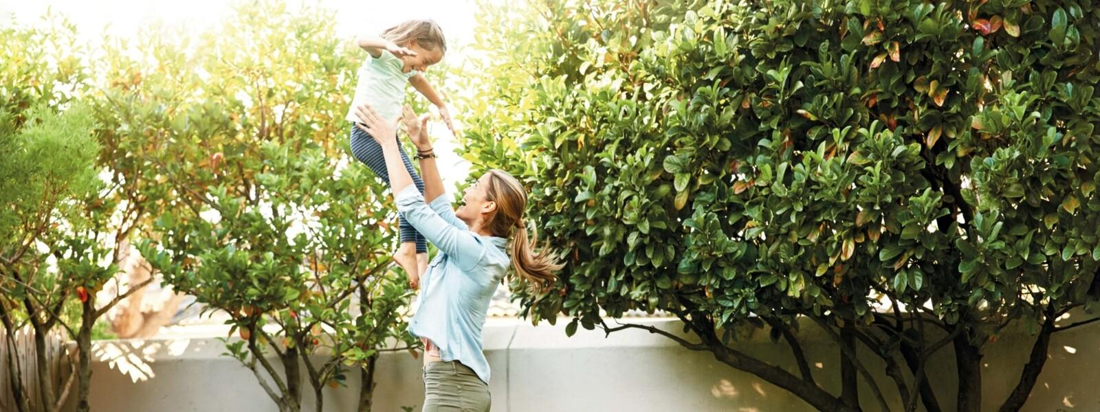 Mutter hebt Tochter in die Luft - im Hintergrund eine Vaillant Wärmepumpe