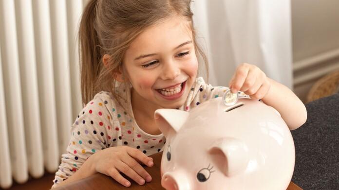 Mädchen wirft Münzen in ein roas farbenes Sparschwein um Geld zu sparen