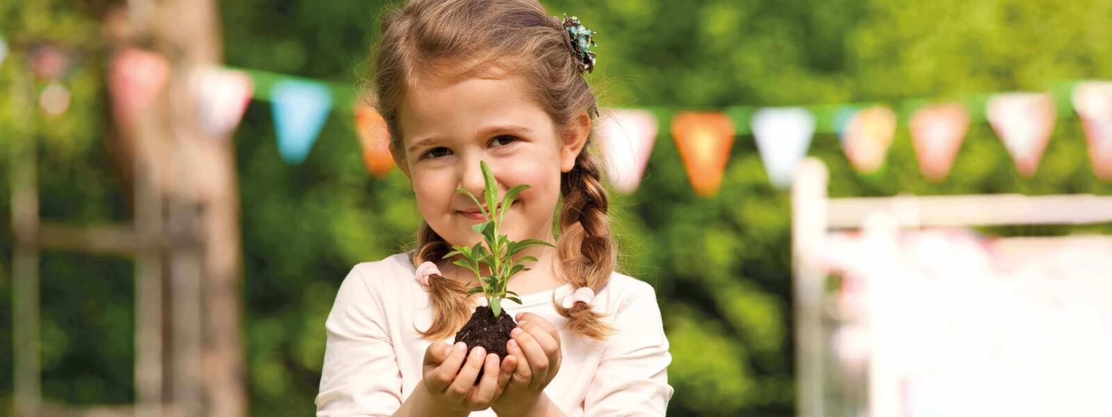 Junges Mädchen steht im Garten und hält ein Pflänzchen in den Händen