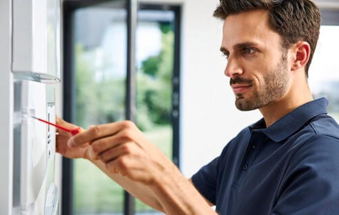 Vaillant Techniker arbeitet mit einem Schraubenzieher an einem Vaillant Gerät