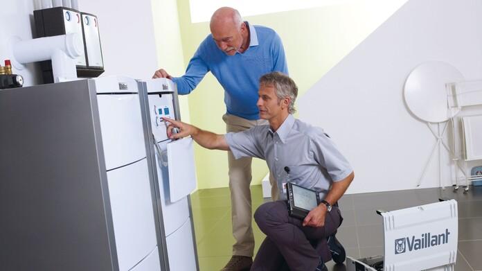Vaillant Kundendiensttechniker führt gerade eine Geräteaktivierung durch und erklärt dem Kunden das Gerät