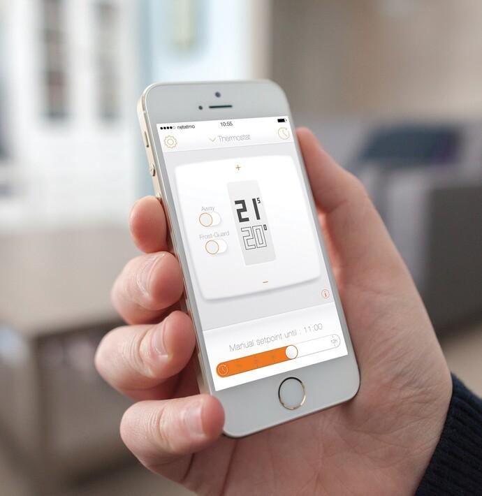 eine Hand hält ein Smartphone in der Hand auf der die Netatmo App zu sehen ist