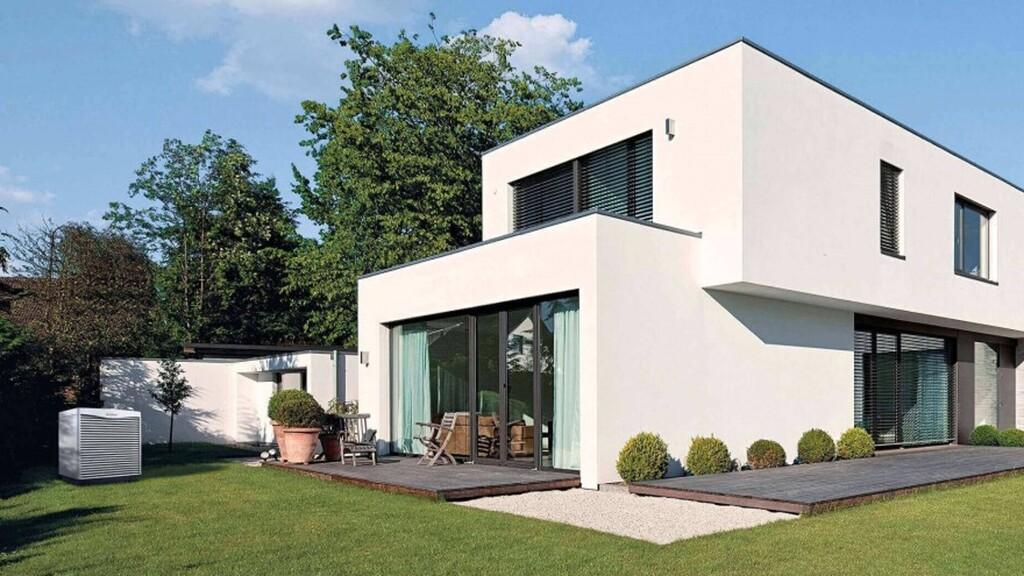Außeneinheit Einer Wärmepumpe Von Vaillant Vor Einem Neu Gebauten Haus,  Umgeben Von Einer Grünen Wiese