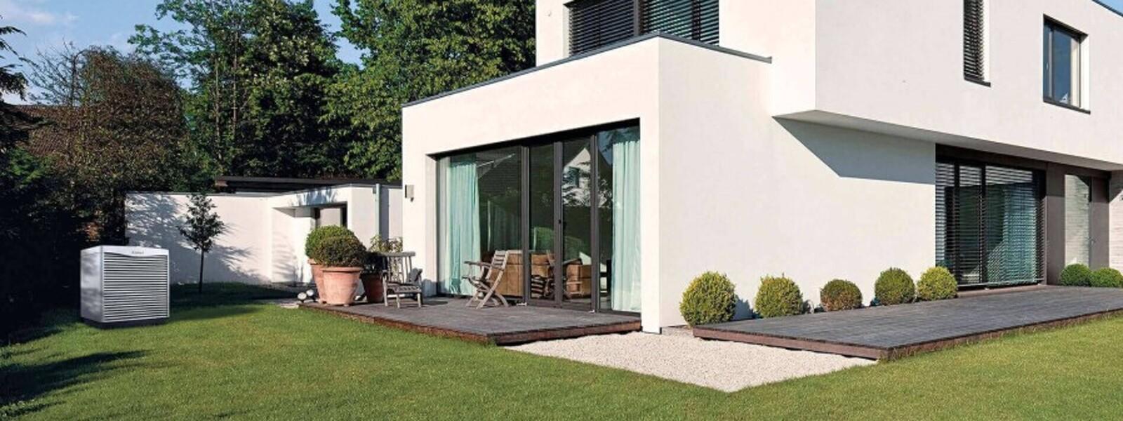 Außeneinheit einer Wärmepumpe von Vaillant vor einem neu gebauten Haus, umgeben von einer grünen Wiese.