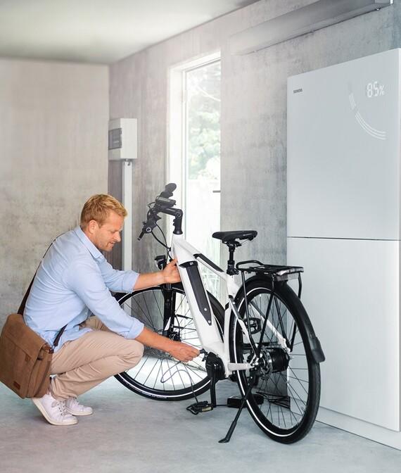 Mann schraubt an seinem Fahrrad, Im Hintergrund steht der Siemens Junelight