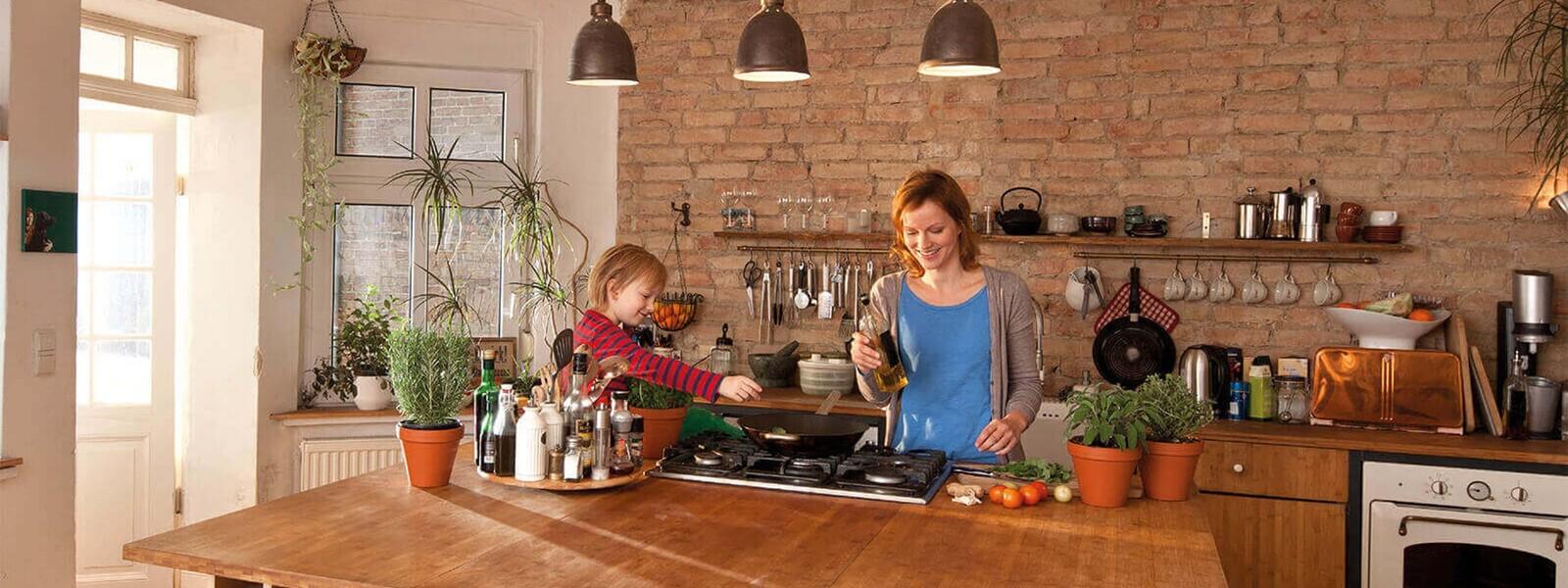 Mutter und Tochter stehen in der Küche und kochen mit einem Gasherd