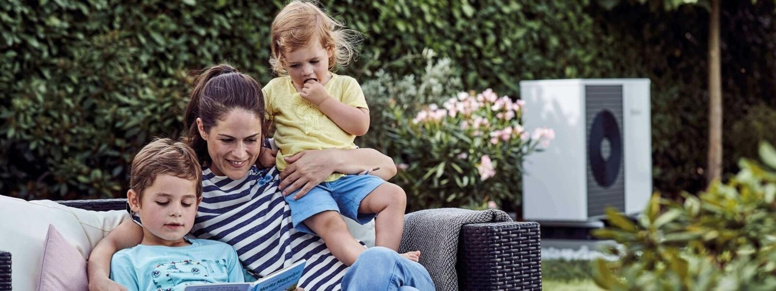 Familie sitzt im Garten, dahinter eine Vaillant Wärmepumpe