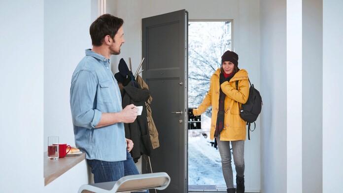 Mann steht im Vorraum und Frau kommt aus der Kälte in ihr beheiztes zu Hause