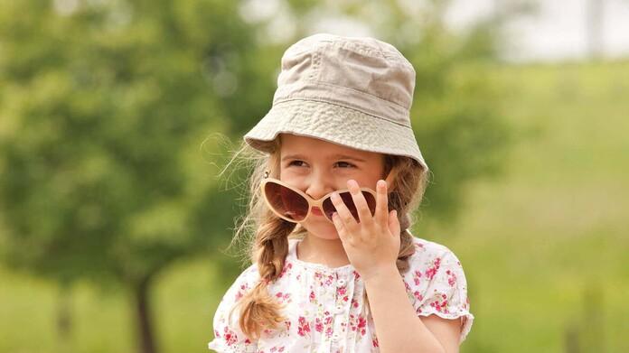 Mädchen mit Sonnenhut steht im Grünen und zieht lässig die Sonnebrille ins Gesicht
