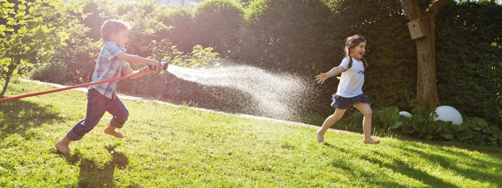 Bub spritzt Mädchen mit Gartenschlauch an